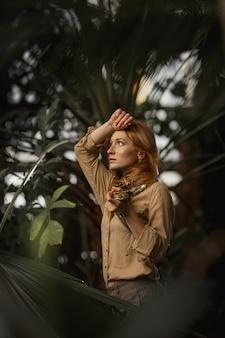 Ein schönes mädchen mit natürlichem make-up und roten haaren steht im dschungel zwischen exotischen pflanzen mit schlange.