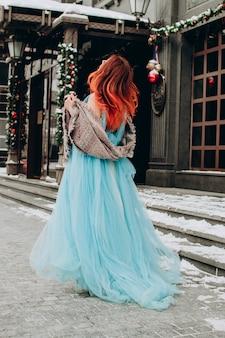 Ein schönes mädchen mit roten haaren in einem langen blauen kleid hat ihr den rücken zugekehrt