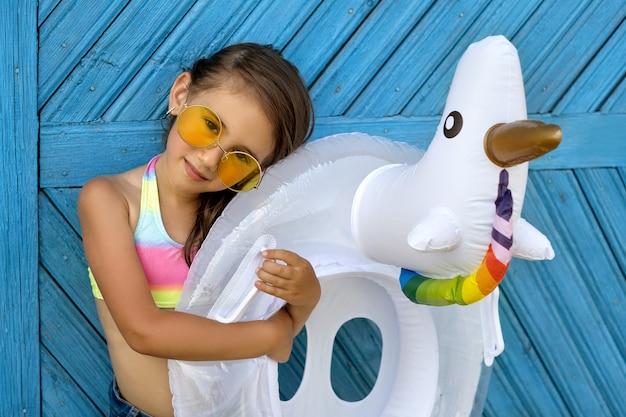 Ein schönes mädchen mit sonnenbrille steht an einer blauen wand mit einem kreis in form eines einhorns