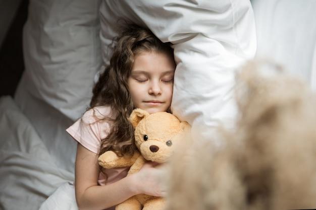 Ein schönes mädchen mit teddybär ein kind mit spielzeug das konzept des kindheitsmorgens