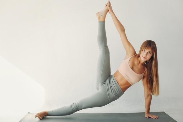 Ein schönes mädchen nimmt an einem yogastudio teil