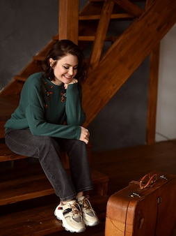 Ein schönes mädchen sitzt neben einem koffer auf einer holztreppe und schaut aus dem fenster