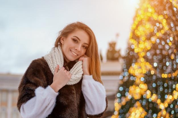 Ein schönes mädchen steht auf dem hintergrund des stadt-weihnachtsbaums