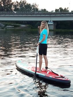 Ein schönes mädchen steht auf einem sup-paddleboard und hält ein ruder über dem kopf vor dem hintergrund des flusses und des waldes