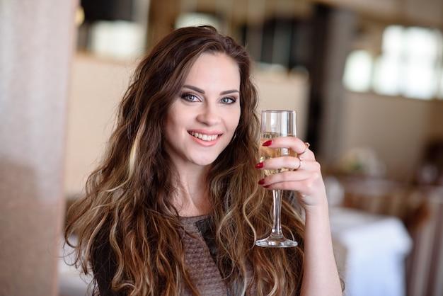 Ein schönes mädchen trinkt champagner in einem restaurant.