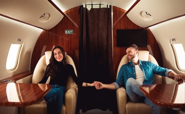 Ein schönes mädchen und ein gut aussehender mann in lässigen outfits halten händchen und lächeln, während sie mit einem privatjet fliegen. Premium Fotos
