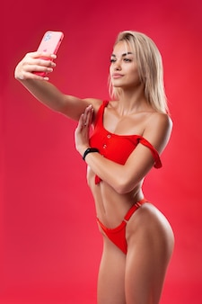 Ein schönes model im badeanzug macht ein selfie zum neuen iphone