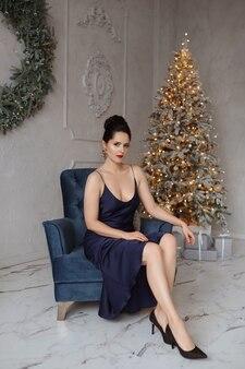 Ein schönes model-mädchen in einem modischen kleid sitzt in einem vintage-sessel im innenraum, der für eine silvesterparty dekoriert ist