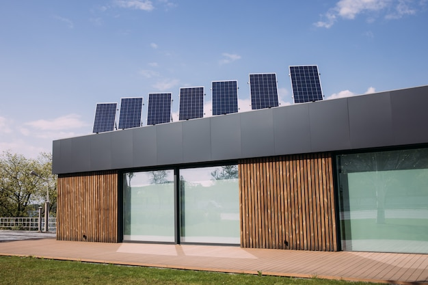 Ein schönes modernes haus in europa baut gerne ein haus mit energieeinsparung, indem es ein solarpanel auf dem dach installiert, um geld zu sparen. das wichtigste ist, die welt zu retten. hintergrund