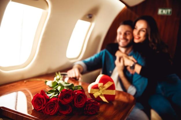 Ein schönes paar feiert den valentinstag in einem privatjet. ein mann gibt seiner freundin ein geschenk in einer roten schachtel
