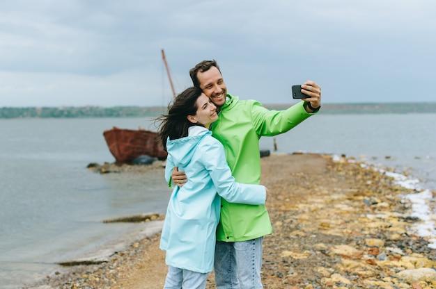 Ein schönes paar in farbigen regenmantel machen ein selfie in der nähe des meeres
