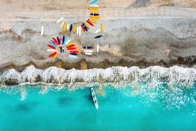 Ein schönes paar liegt am strand von frankreich neben surfbrettern und schießt von einem quadcopter aus. viele surfbretter liegen ungewöhnlich am strand.