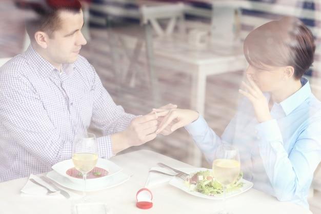 Ein schönes paar verlobt sich mit einem restaurantfoto, das durch ein fenster aufgenommen wurde