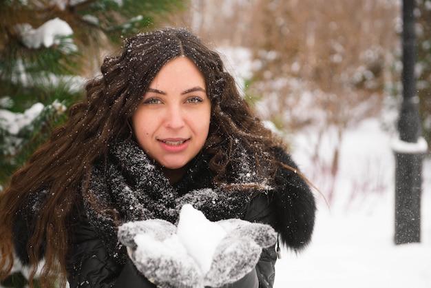 Ein schönes porträt der schwangeren frau im freien im verschneiten park