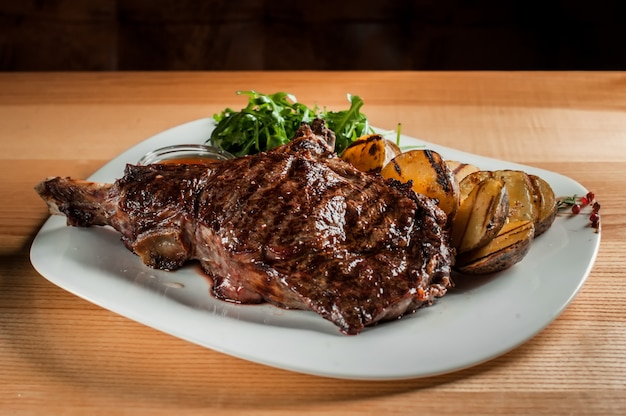 Ein schönes saftiges steak mit salat auf platte ist auf dem holztisch.