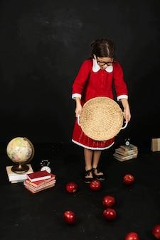 Ein schönes schulmädchen in einem roten kleid mit äpfeln und einer kugel der bücher auf einem schwarzen hintergrund
