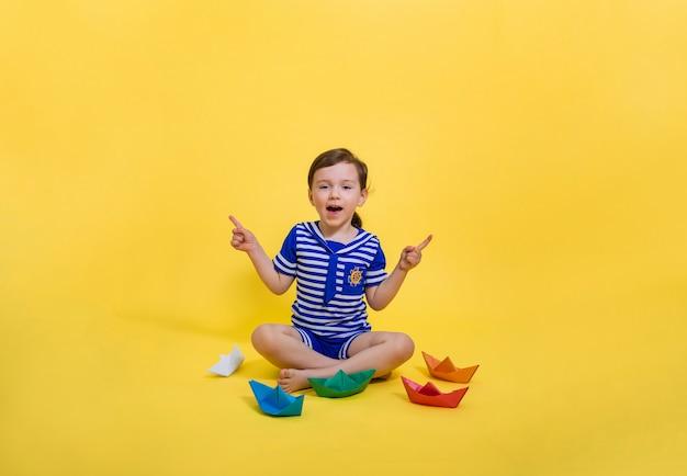 Ein schönes seemannsmädchen zeigt mit den fingern zur seite und sitzt auf einem gelben, isolierten raum. das mädchen machte origami aus papier. bunte papierschiffe.