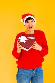 Ein schönes sexy mädchen in einem hut des neuen jahres und einem roten pullover, der ein geschenk in ihren händen hält. weihnachten oder silvester auf gelbem hintergrund feiern