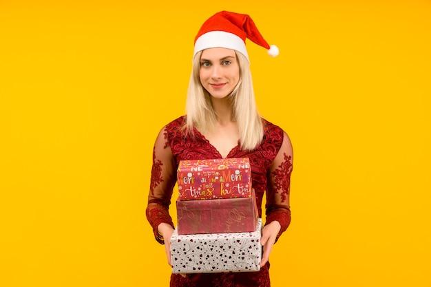 Ein schönes sexy mädchen in einem neujahrshut und einem grauen kleid, halten in den händen geschenke auf gelbem hintergrund. weihnachts- oder neujahrsfeier