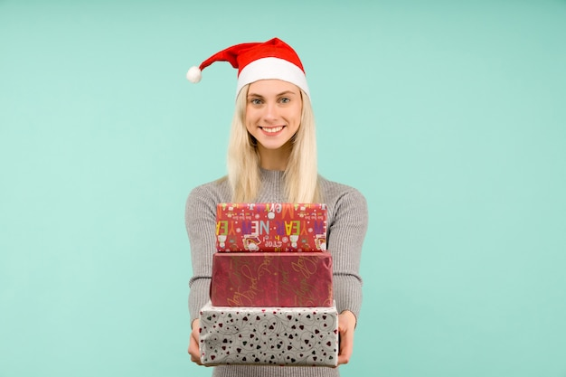 Ein schönes sexy mädchen in einem neujahrshut und einem grauen kleid, halten in den händen geschenke