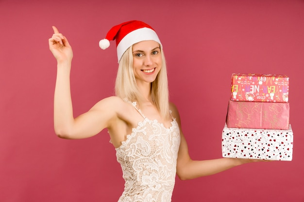 Ein schönes sexy mädchen in einem neujahrshut und einem weißen kleid halten in händen geschenke zeigt finger nach oben