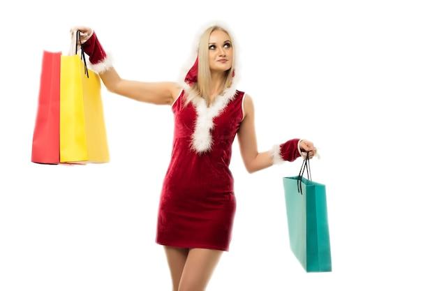 Ein schönes sexy mädchen in einem neujahrskleid, halten in den händen einkaufstaschen lokalisiert auf weiß. weihnachtsfeier oder neujahrsverkauf