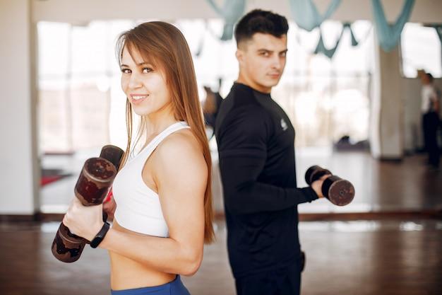 Ein schönes sportpaar nimmt an einer turnhalle teil
