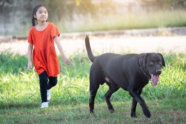 Ein schönes südostasiatisches mädchen in roten outfits spielt abends mit ihrem großen hund im hinter- oder vorgarten. konzept für tierliebhaber