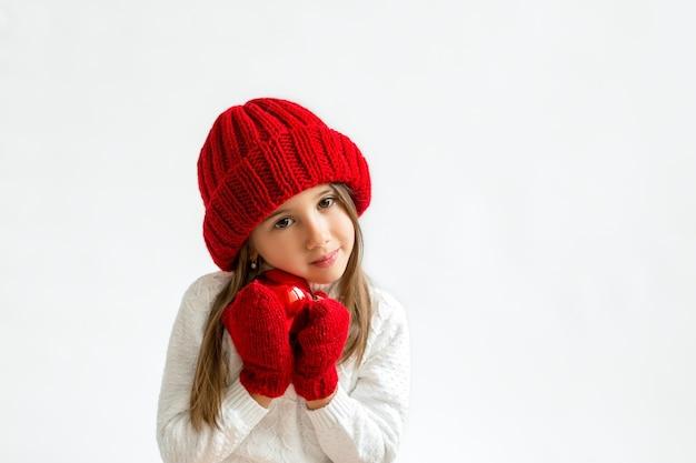 Ein schönes süßes mädchen in einem strickpullover hält einen roten weihnachtsball mit zärtlichkeit