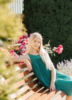 Ein schönes teenager-mädchen mit langen blonden haaren sitzt auf einer bank in einem blühenden park