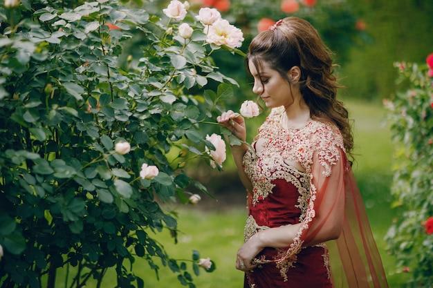 Ein schönes türkisches mädchen in einem langen roten kleid geht in die alte stadt des sommers