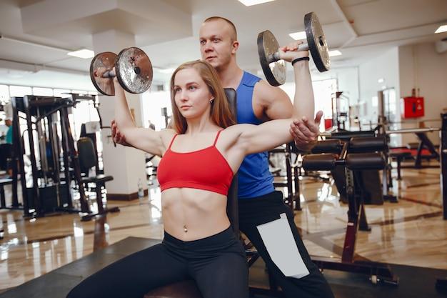 Ein schönes und athletisches sportkleidungsmädchen, das in der turnhalle mit freund ausbildet