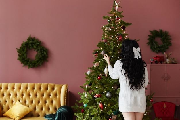 Ein schönes vorbildliches mädchen in einem weißen strickkleid, das mit ihrem rücken steht und den weihnachtsbaum schmückt