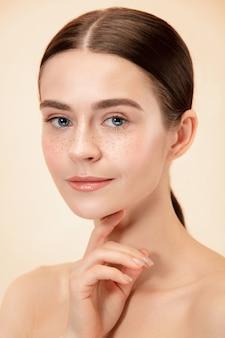 Ein schönes weibliches gesicht. perfekte und saubere haut der jungen kaukasischen frau auf pastellstudiohintergrund.