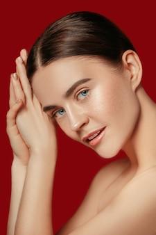 Ein schönes weibliches gesicht. perfekte und saubere haut der jungen kaukasischen frau auf rotem studio.