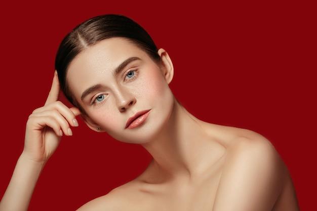 Ein schönes weibliches gesicht. perfekte und saubere haut der jungen kaukasischen frau auf rotem studiohintergrund.