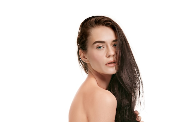 Ein schönes weibliches gesicht. perfekte und saubere haut der jungen kaukasischen frau auf weißem studiohintergrund.