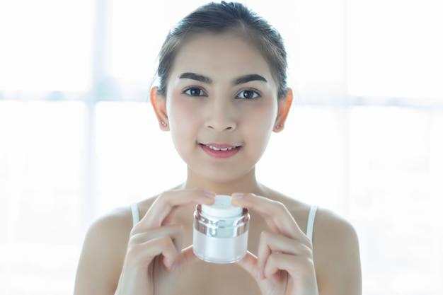 Ein schönheitsasiat, der ein hautpflegeprodukt, eine feuchtigkeitscreme oder eine lotion kümmert sich um ihrem trockenen teint verwendet. feuchtigkeitscreme in weiblichen händen.