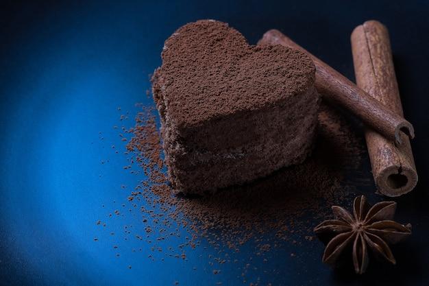 Ein schokoladendessert in form eines mit kakaopulver bestreuten herzens liegt auf einem dunklen hintergrund neben zimt. ein foto mit einem platz unter dem seitentext