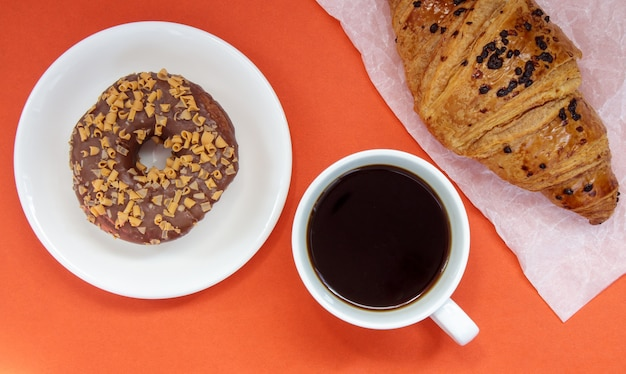 Ein schokoladendonut, croissant und schwarzer americano-kaffee ohne milch in einer weißen tasse auf hellem hintergrund. ansicht von oben, flach. frisch gebrühtes oder instant-heißkaffeegetränk mit süßem gebäck.