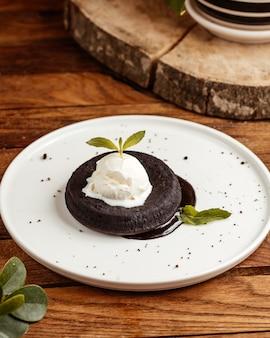 Ein schokoladenkuchen der draufsicht mit sahne-innenplatte auf der braunen hölzernen tischkuchen-dessertschokolade