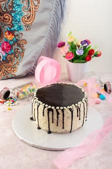 Ein schokoladenkuchen der vorderansicht mit süßigkeiten auf dem rosa schreibtisch