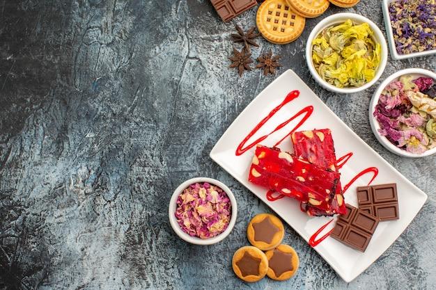 Ein schokoladenteller mit keksen und trockenen blumen auf grau