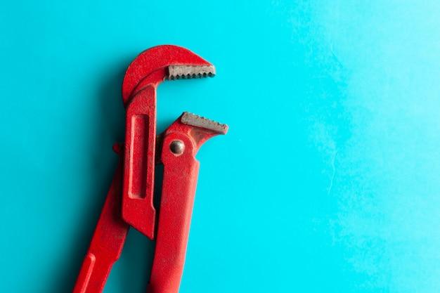 Ein schraubenschlüssel auf dem blauen hintergrund mit einigen passenden verbindungsstücken. für design und dekoration