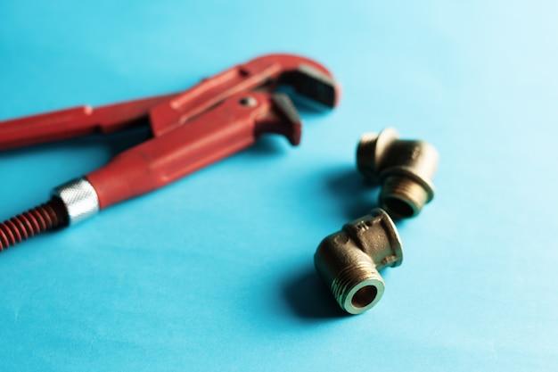 Ein schraubenschlüssel auf dem blauen hintergrund mit einigen passenden verbindungsstücken