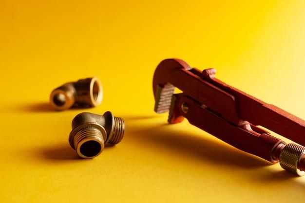 Ein schraubenschlüssel auf dem gelben hintergrund mit einigen passenden verbindungsstücken. für design und dekoration