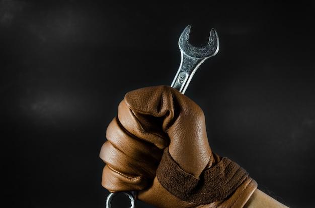 Ein schraubenschlüssel hielt von lederhandschuh mann hand in dunkelem licht