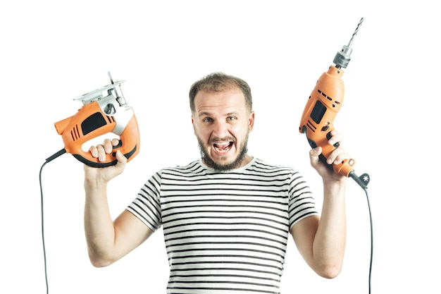 Ein schreiender mann in einem gestreiften t-shirt hält einen bohrer und eine elektrische stichsäge in den händen isoliert