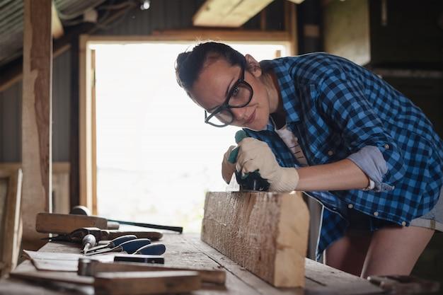 Ein schreiner beschäftigt sich mit holz in einer heimwerkstatt, gehobelte hobelmaschinenbretter aus holz