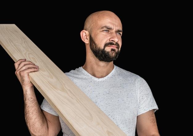 Ein schreiner in einem weißen t-shirt mit einem escheboard bereit. wegschauen. auf schwarzem hintergrund. isolieren